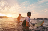 Fit couple surfing at sunset - Surfers friends having fun inside ocean - Extreme sport, travel, healthy lifestyle and vacation concept - Focus on man head