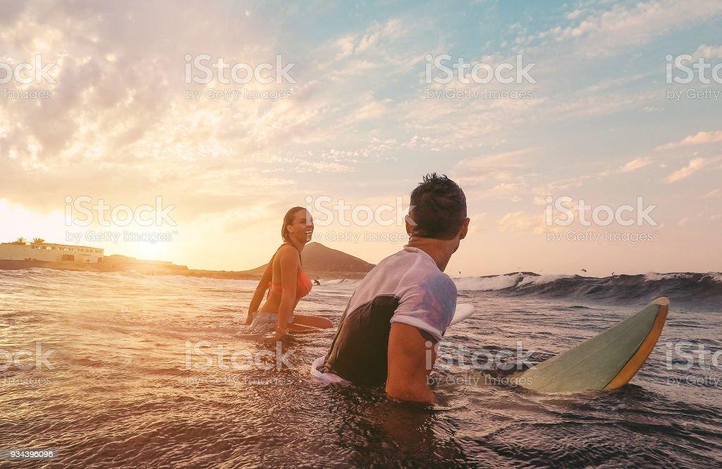 Passen paar Surfen bei Sonnenuntergang - Surfer-Freunde, die Spaß im Inneren Ozean - Extreme Sport, Reisen, gesunde Lebensweise und Urlaub Konzept - Fokus auf Kopf – Foto