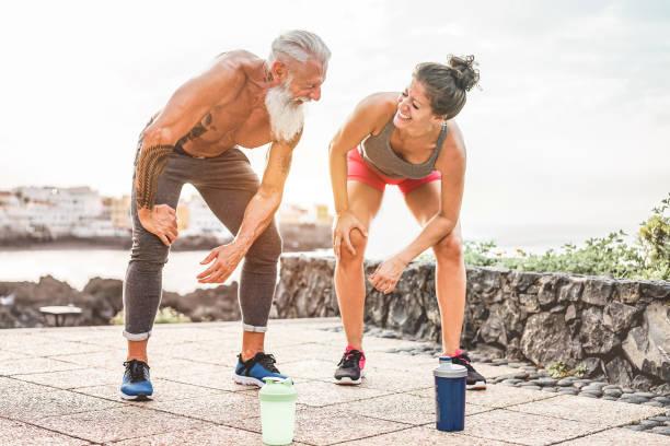 fit paar rast nach schnell laufenden training - jogger im freien training bei sonnenuntergang zusammen - main konzentrieren sich auf mann gesicht - fitness, sport, wellness, training, fitness-studio und gesunden lifestyle-konzept - laufende tattoos stock-fotos und bilder