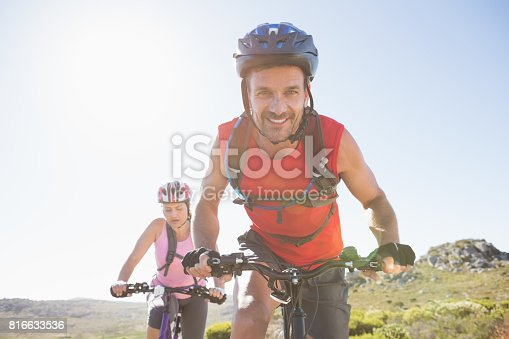 istock Fit cyclist couple riding together on mountain trail 816633536