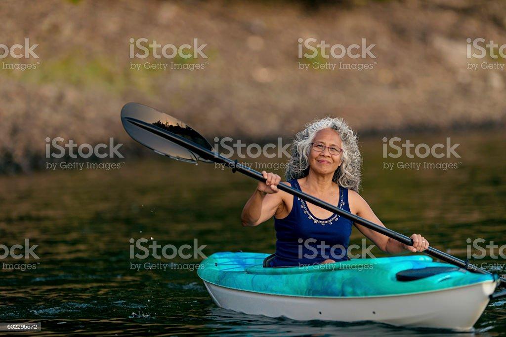 Fit elderly woman kayaking stock photo