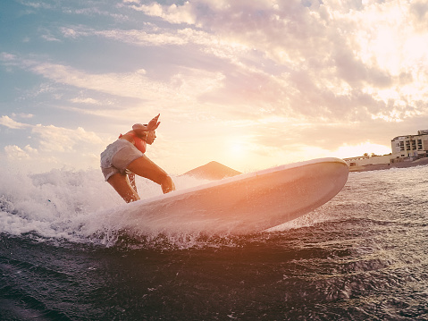 istock Fit female athlete surfing at sunset - Surfer woman performing outdoor inside ocean- Extreme sport, healthy lifestyle, adventure and vacation concept - Focus on her body 924798222