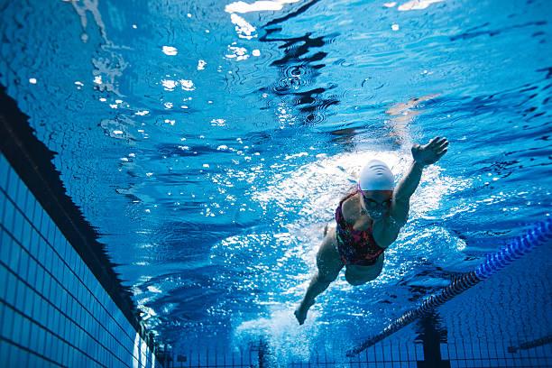 fit atleta femenina nadando en la piscina - natación fotografías e imágenes de stock