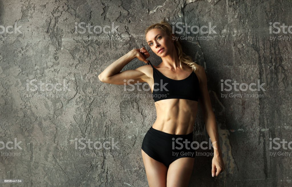 Fit female fitness model posing and showing her muscular body with strong and tanned abdominal muscles in front of concrete wall stock photo