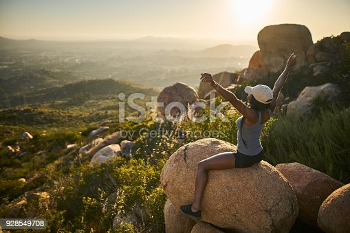 istock fit female hiker sitting on rock at mountain top looking at city in distance with arms up 928549708