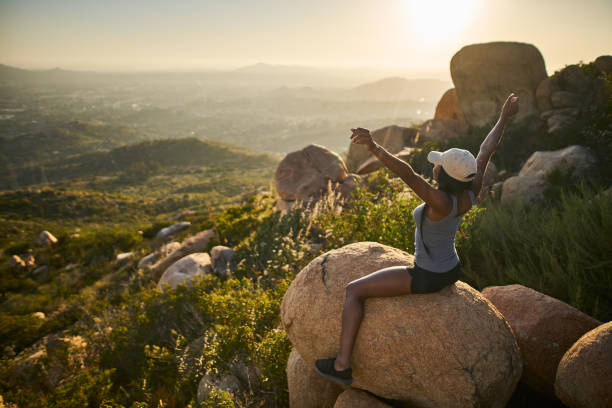 fit female hiker sitting on rock at mountain top looking at city in distance with arms up stock photo