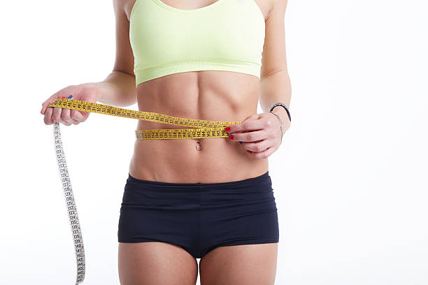 fit female measuring her waist stock photo