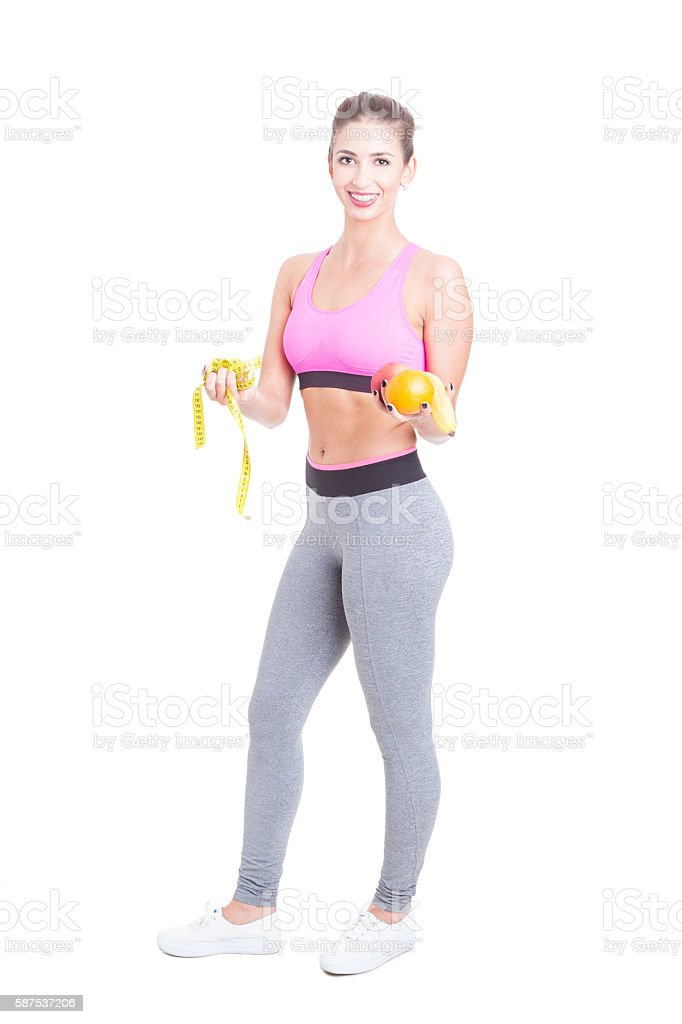 Fit female standing holding fruits and tape line stock photo