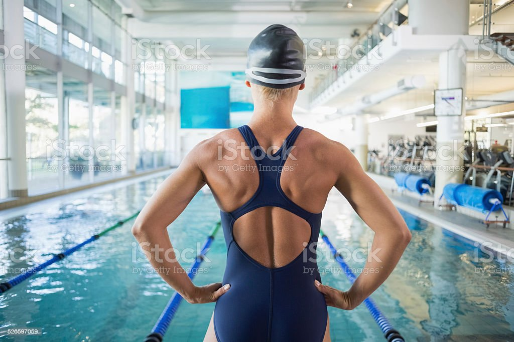 Fit female swimmer by pool at leisure center stock photo