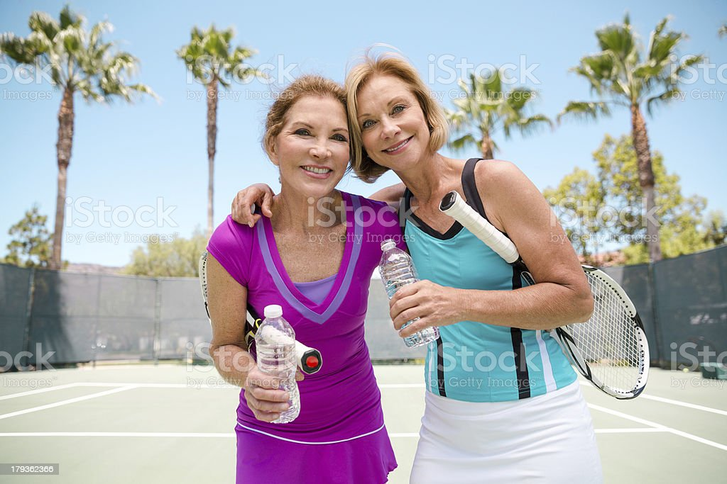 Fit friends playing tennis stock photo
