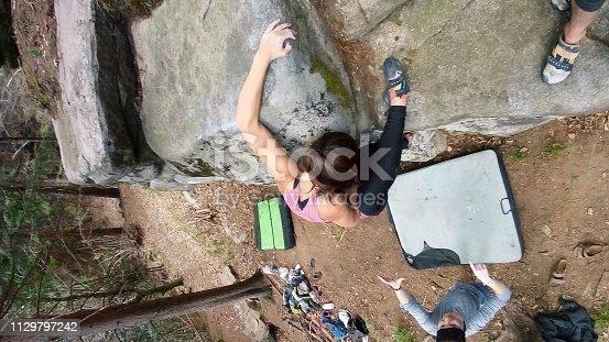 Fit girl boulder climbing big granite rocks in Croatia