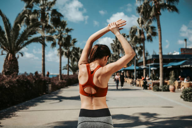 Fit girl doing sport exercise outside on seafront Concentrated slim young woman is raising her arms while warming up before jogging. She is standing while turning her back to camera. Summer activity concept bra stock pictures, royalty-free photos & images