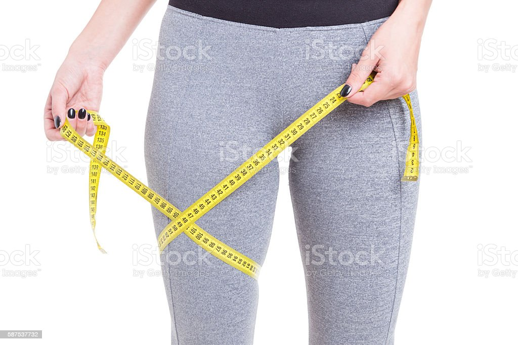 Fit girl holding tape line around leg stock photo