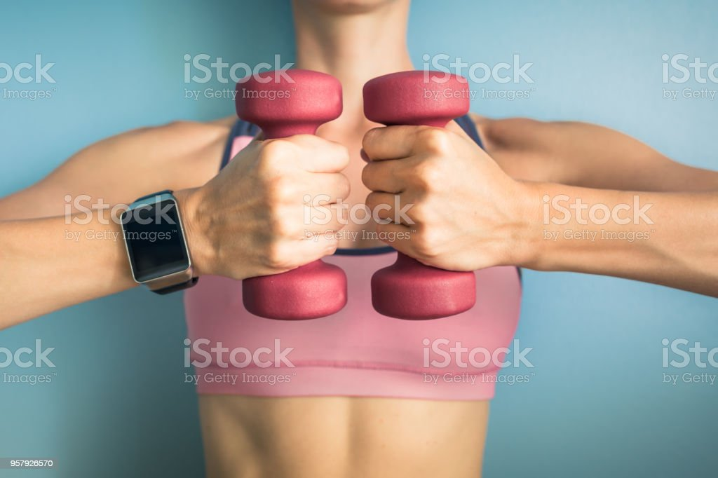 Fit girl holding weights and wearing smartwatch. stock photo