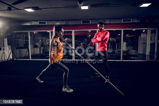 istock Fit girl lifting heavy bar in a gym while her personal trainer in looking at her . 1043287682