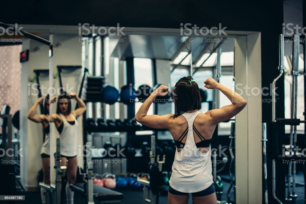 Fit Girl Looking In Mirror Stock Photo & More Pictures of Activity
