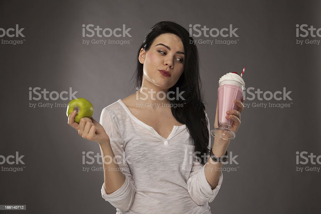 Fit girl making healthy decisions with apple and milkshake stock photo