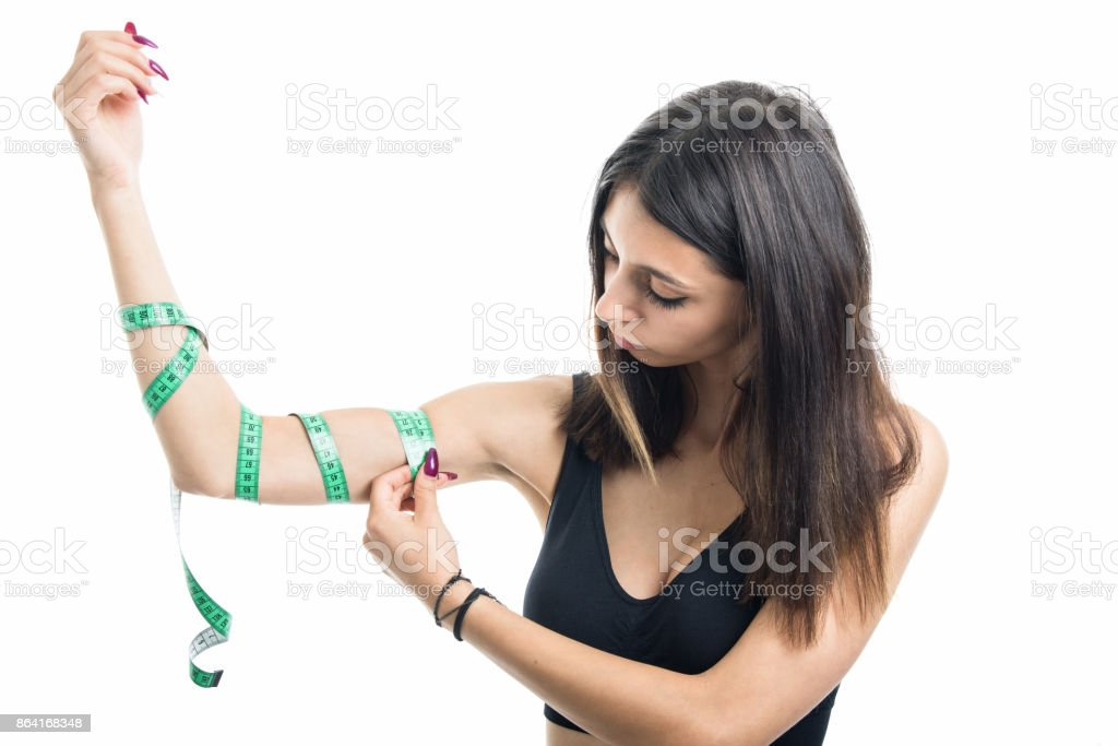 Fit girl measuring arms with tape royalty-free stock photo