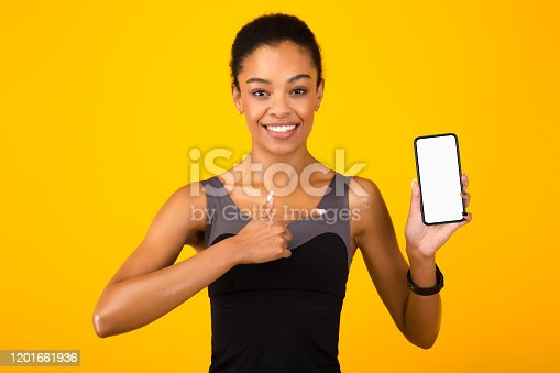 1132512759 istock photo Fit Girl Pointing Finger Showing Smartphone Screen Over Yellow Background 1201661936