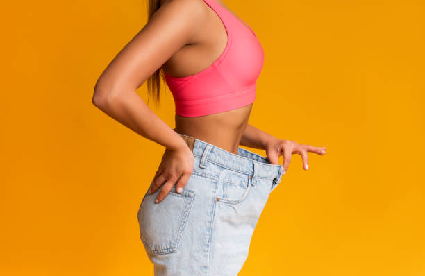 Fit Girl Posing In Oversize Jeans Over Yellow Background Weight Loss Concept. Profile Portrait Of Fit Girl Posing In Oversize Jeans Over Yellow Background, Cropped Image With Copy Space dieting stock pictures, royalty-free photos & images