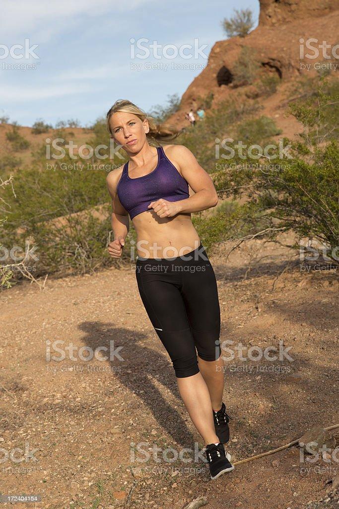 Fit girl running thru desert royalty-free stock photo