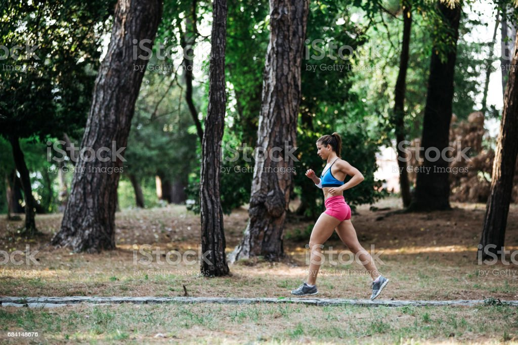 Fit girl runs in the forest foto stock royalty-free