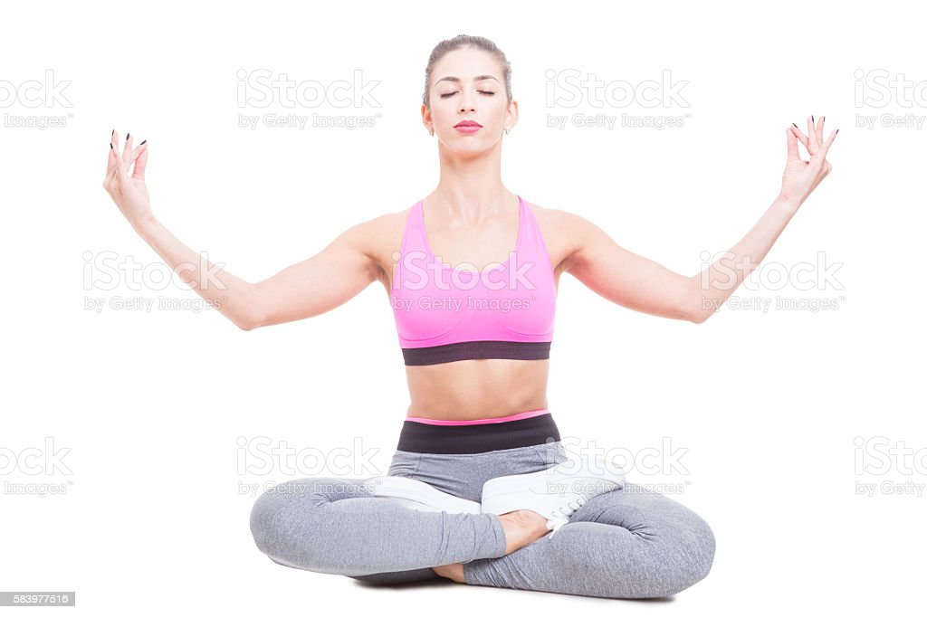 Fit girl sitting in lotus position and meditating stock photo