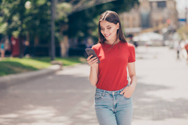 fit girl smiling and looking into the phone holding her hand in the pocket of blue jeans on a hot summer day - teenage girls stock pictures, royalty-free photos & images
