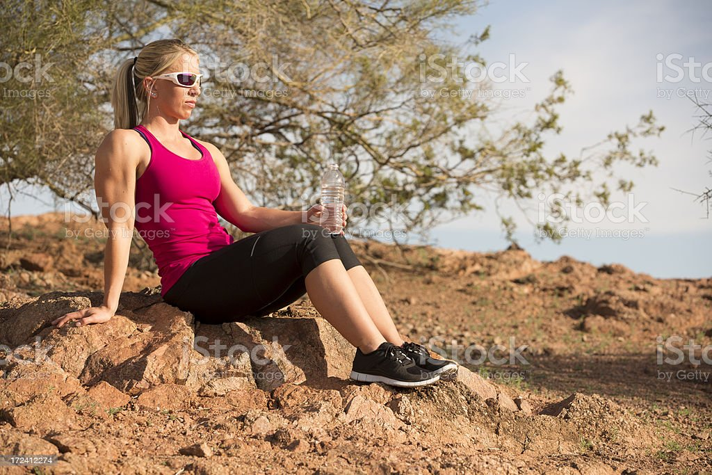 Fit girl taking a break from running in the desert royalty-free stock photo