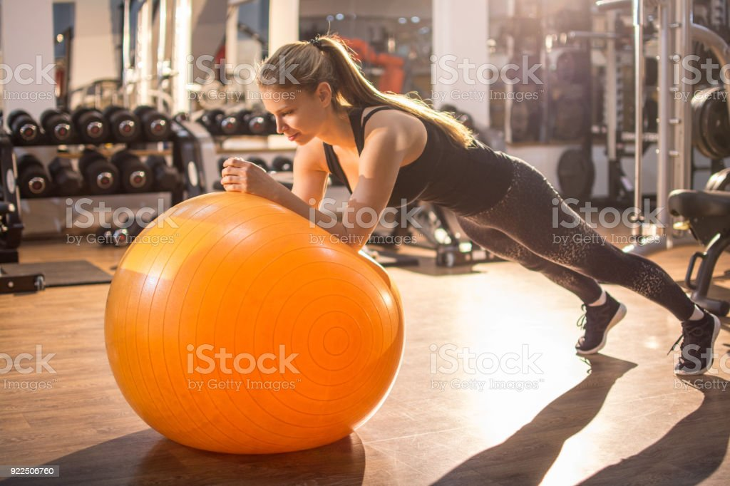 Fit girl workout with fitness ball in plank position in gym. stock photo