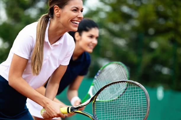 fit gelukkige mensen die samen tennis spelen. sport concept - tennis stockfoto's en -beelden