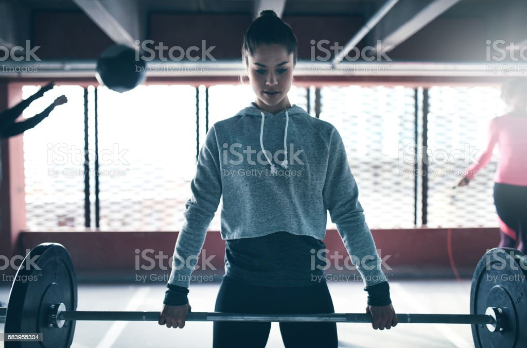 Fit healthy woman lifting a weight barbell stock photo