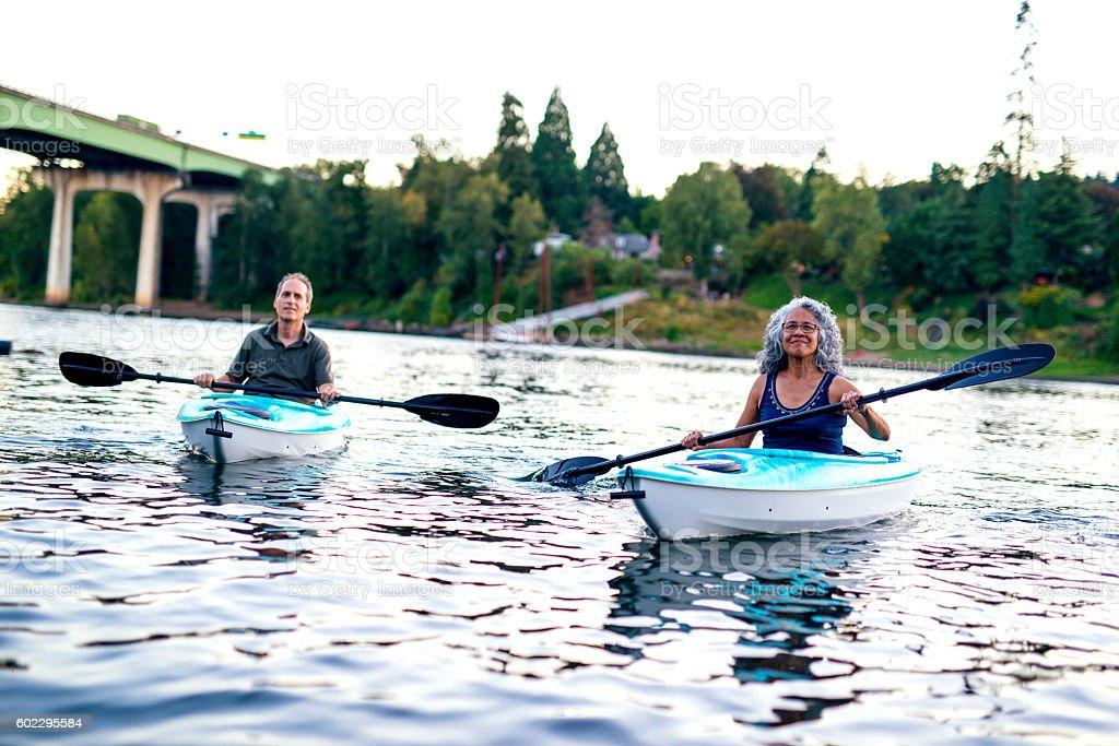 Fit heterosexual couple kayaking together stock photo
