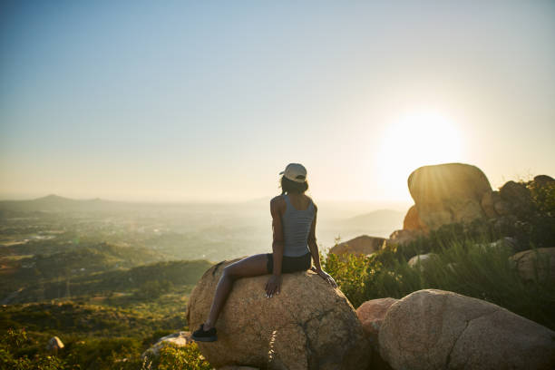fit hiker at top of mountain sitting on huge rock watching sun set stock photo