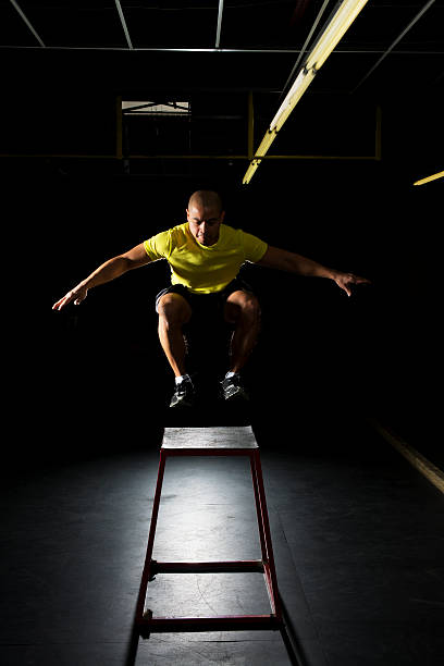 A fit male in workout gear box jumping stock photo
