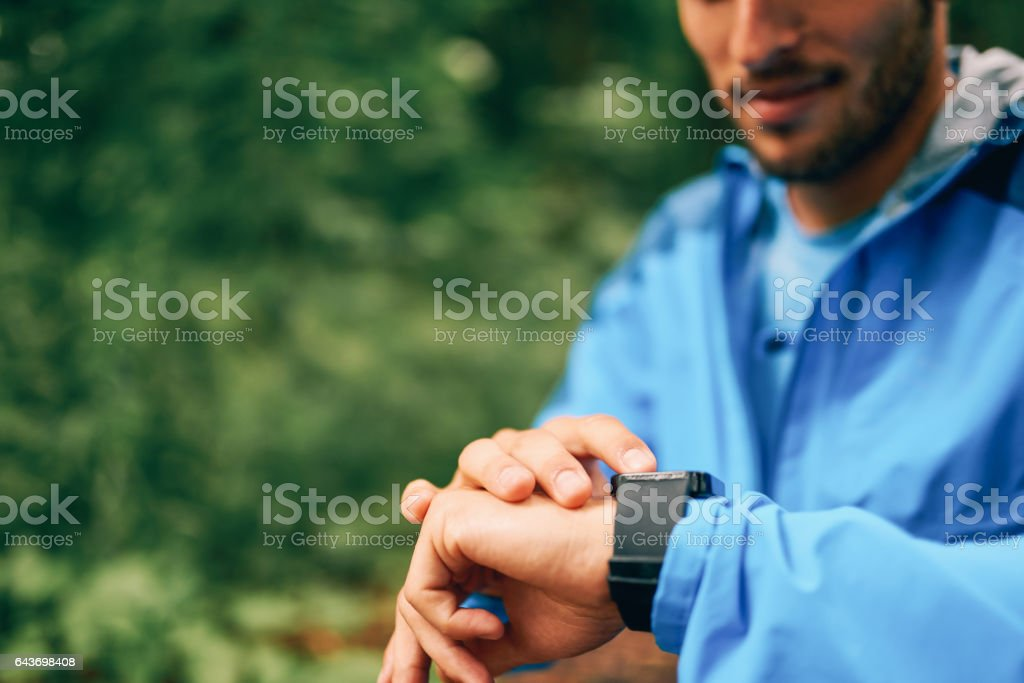 Fit male jogger day using a smartwatch during cross country forest trail race in a nature park stock photo