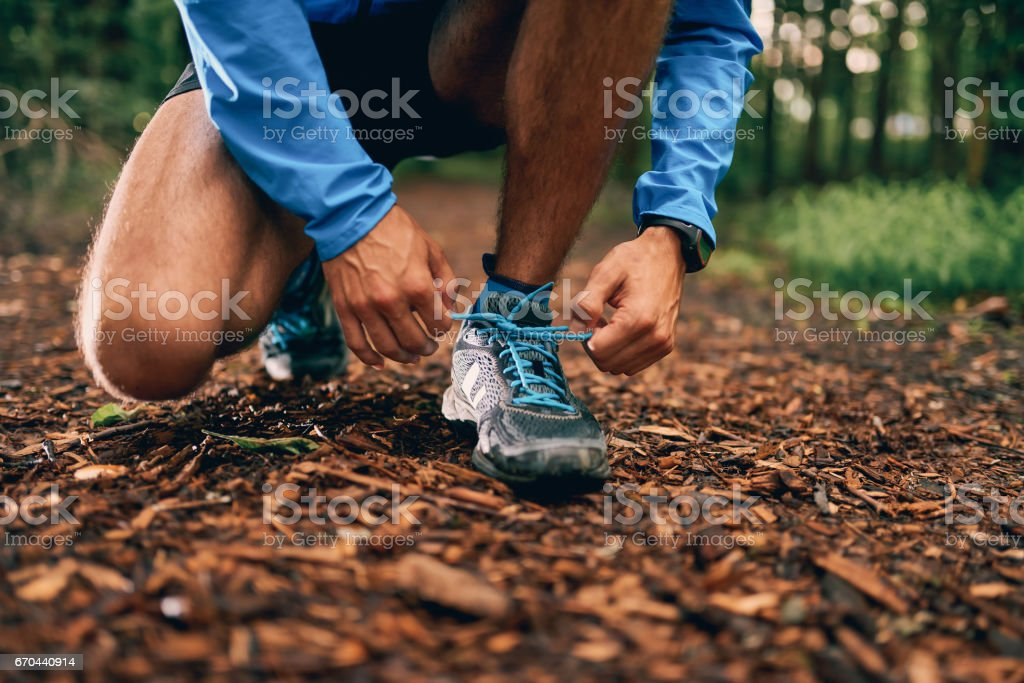 Fit male jogger ties shoes while day training for cross country forest trail race in a nature park – Foto