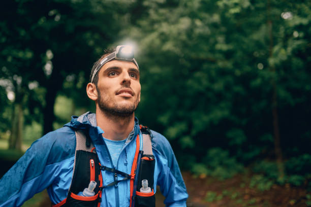 Fit male jogger with a headlamp rests during training for cross country trail race in nature park stock photo
