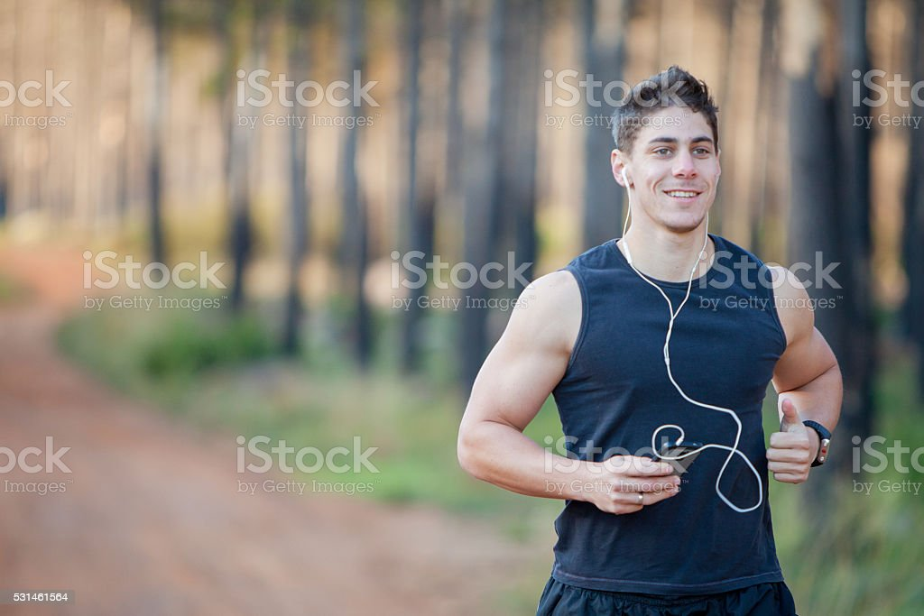 Fit male jogging and listening to music stock photo