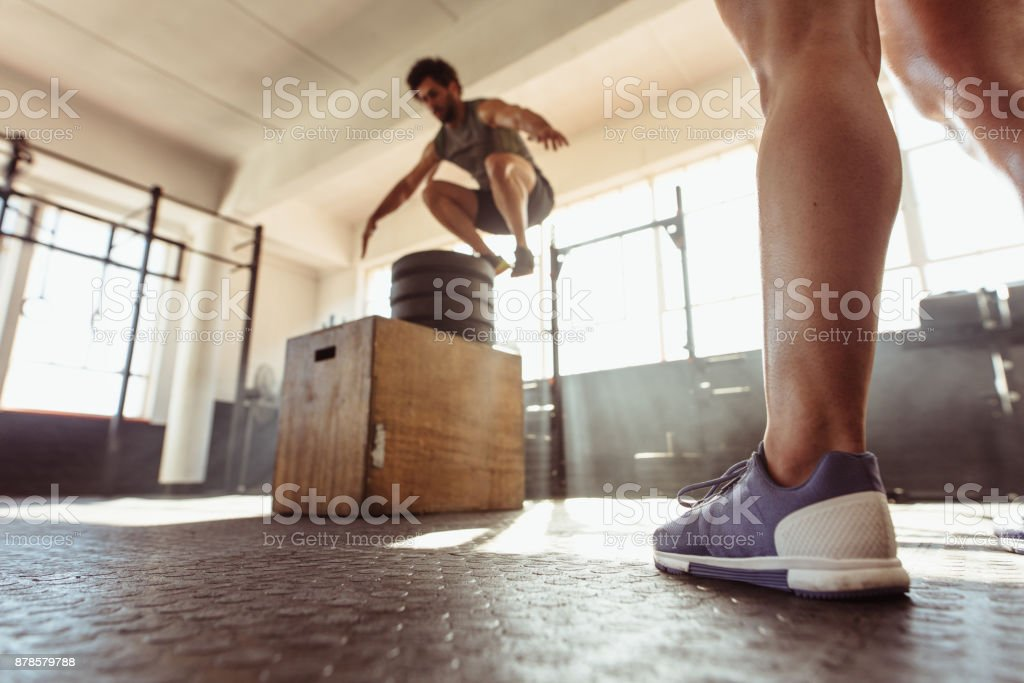 Fit man box jumping at cross training gym stock photo