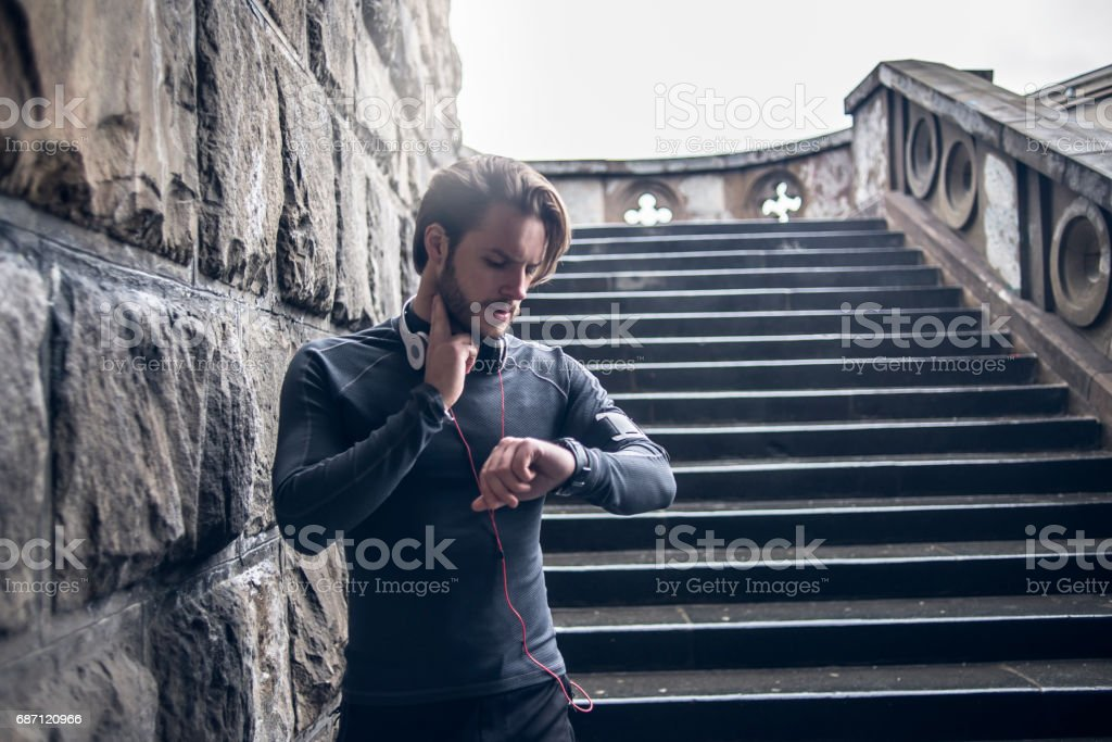 fit man checking his pulse after workout stock photo