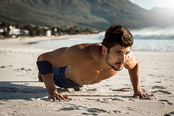 fit man doing push ups on the beach stock photo