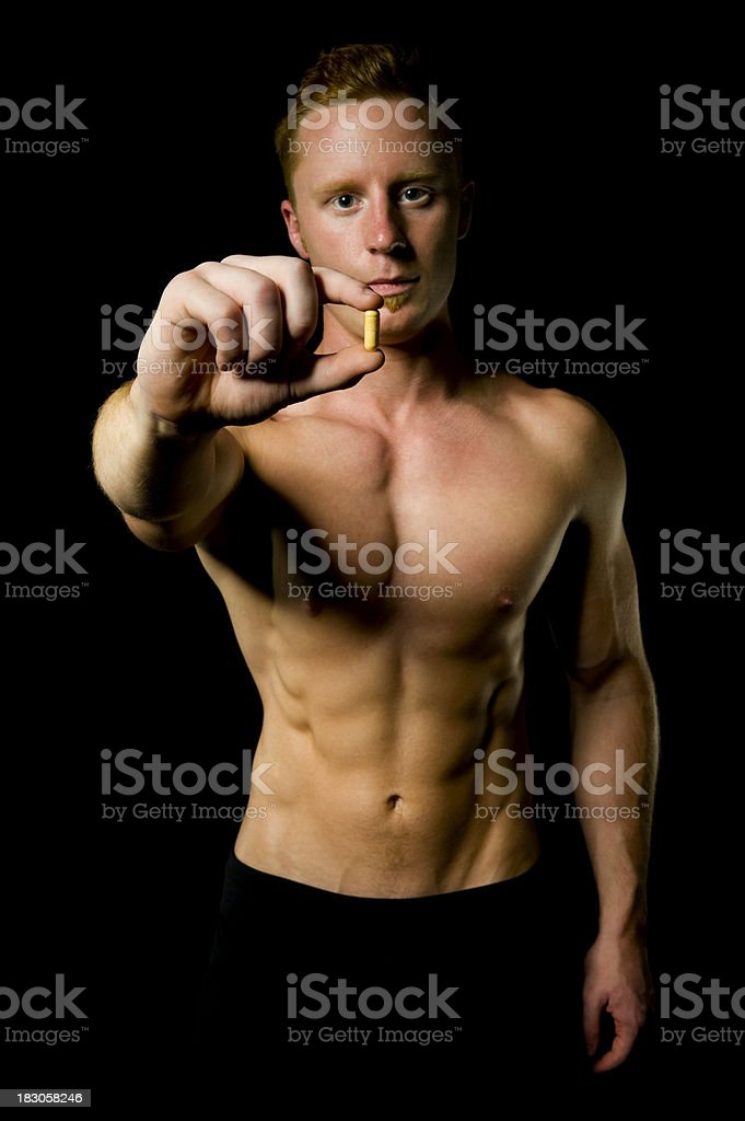 Fit man holding a pill royalty-free stock photo