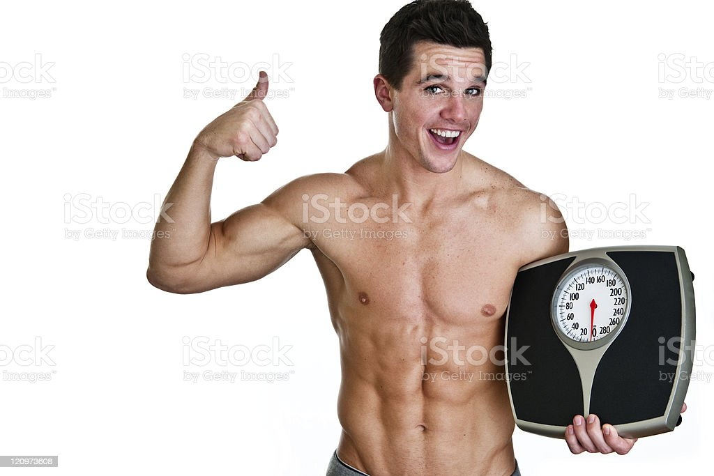 Fit man holding a scale givings thumbs up royalty-free stock photo