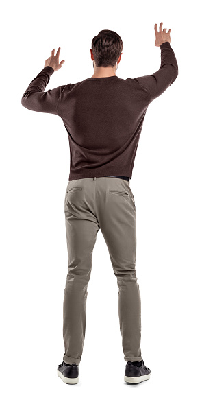 istock A fit man in casual sweater stands in a back view with both arms lifted up to manipulate an invisible touch screen. 1070109300