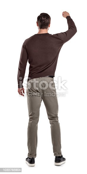 A fit man in casual sweater stands in a back view with one arm lifted up as if holding something in front of him. Careful hold. Showing something in hand. Back view on man.