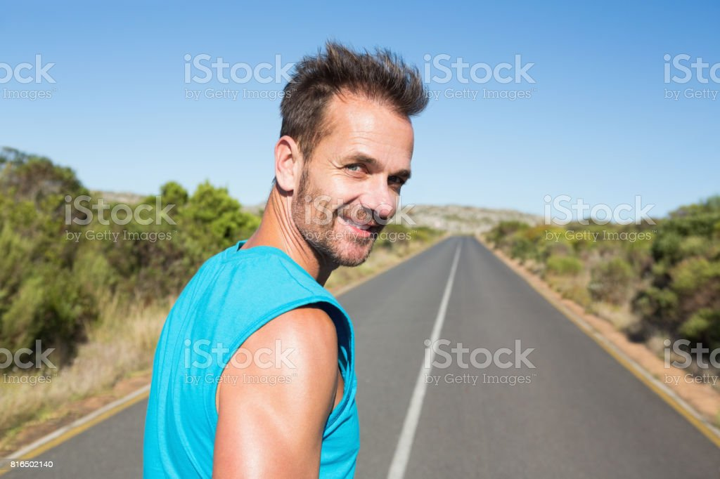 Fit man jogging on the open road smiling at camera stock photo