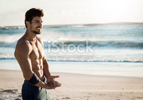 519676858istockphoto fit man relaxing on the beach 519676442