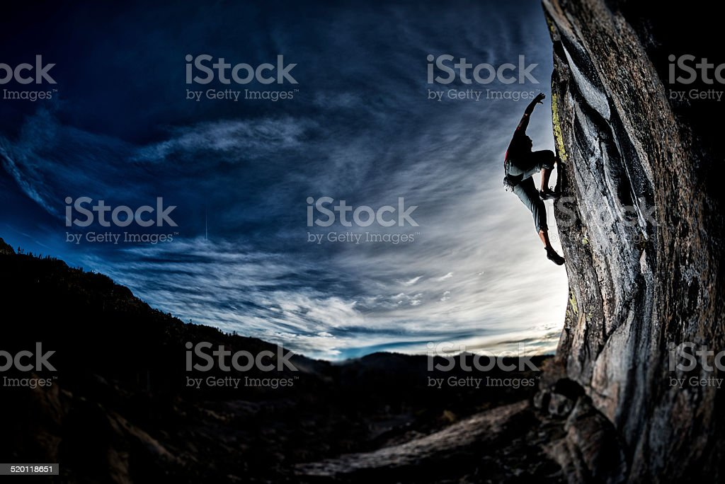 Fit man rock climbing at sunset stock photo