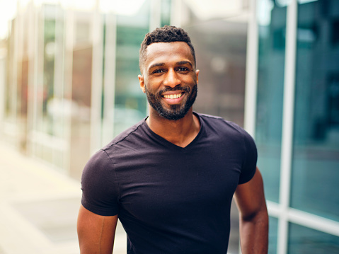 A fit black man with a beard, standing outdoors in a city area.